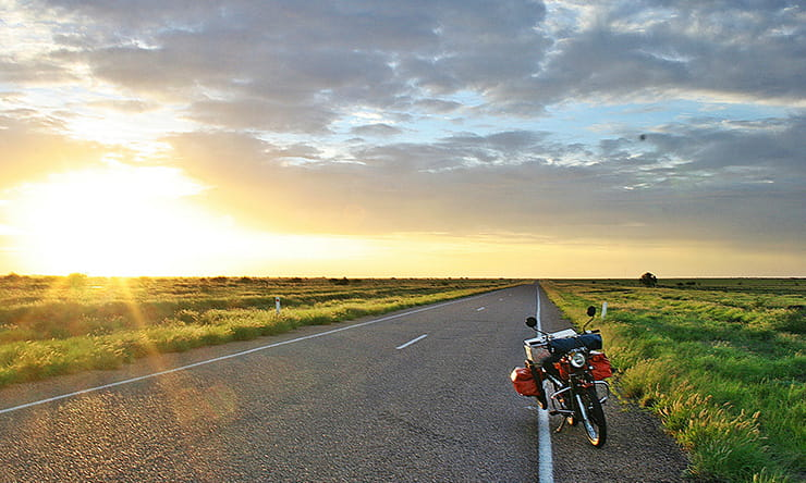 the sunsets while a motorcycle sits at the side of the road