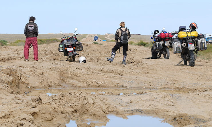 A group of motorcyclists look at a rutted road