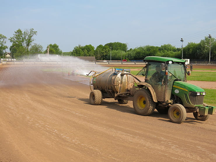 a tractor waters the circuit for sliding bikes on