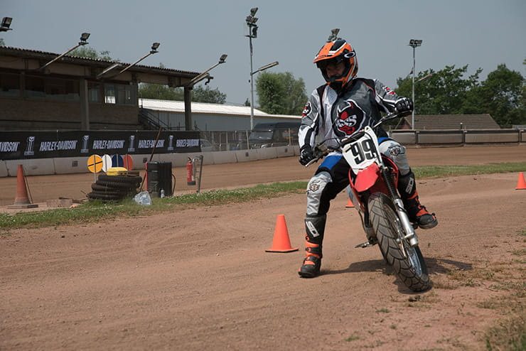 Kane practicing manoeuvres on a flat track bike