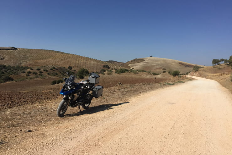 blue motorbike at the edge of a gravel road on a motorcycle touring trip
