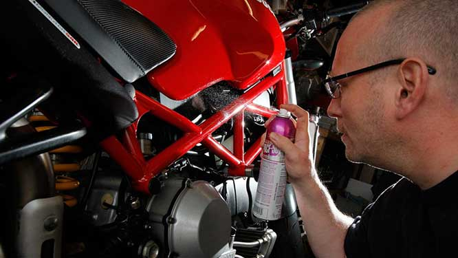 Corrosion protectant being sprayed on a red motorcycle