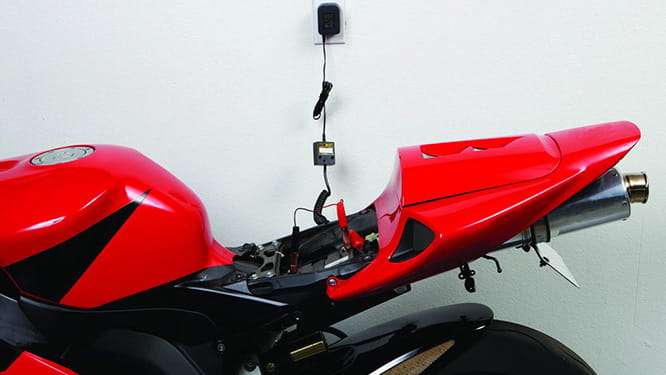 Red motorbike connected to a trickle charger during winter
