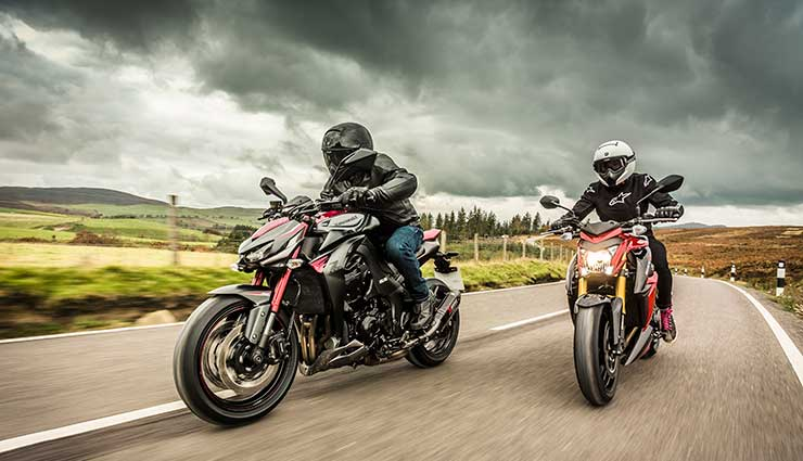 Two motorcyclists ride under dark clouds in the winter