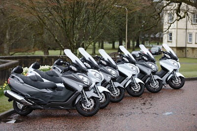 Suzuki Burgman 650 Executive's line-up for duty. Spot the odd one out.