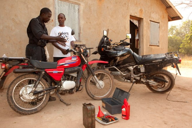 Sulayman Senghore,a Riders mechanic checks health worker Bubbacarr Jallow's motorcycle in The Gambia.