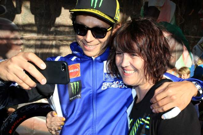 Valentino Rossi helps a fan to a selfie at the Day of Champions in August 2014