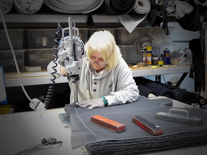Evelyn cuts out garment sections using a band knife. It's lethally sharp which is why she is wearing a chain mail glove.
