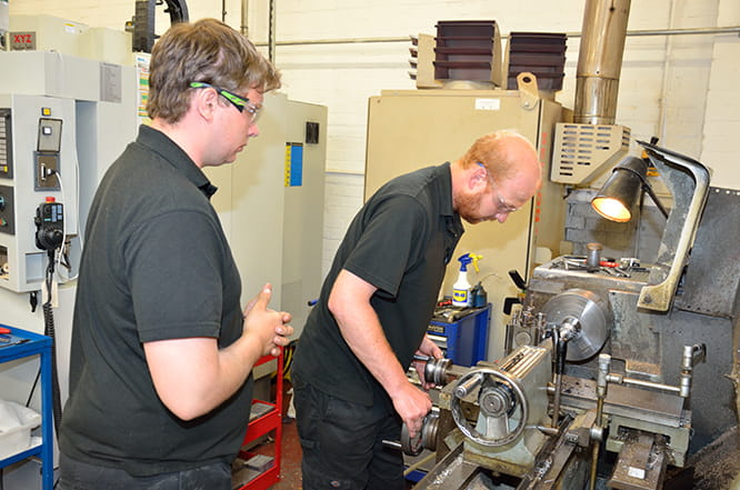 Some machining is still carried out on a manual lathe. Chief designer Sean does the work watched closely by recent recruit and Pit Bike racer Eliot.