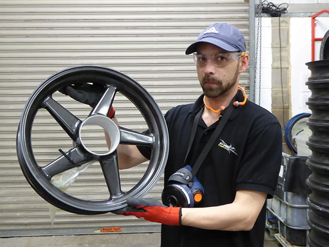 Machinist Chris Slade with a Dymag composite wheel. The construction is modular. Model specific hubs are bonded into place before final inspection takes place.
